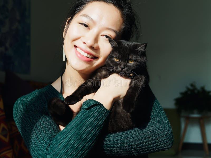 Het portret van mooi Chinees jong meisje koestert haar leuke Britse Shorthair-Kat die thuis verbazende oranje ogen en glimlach he stock afbeeldingen