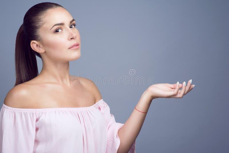 Het portret van mooi donker-haired meisje met perfecte huid en naakt maakt omhoog het tonen van lege palm voorstellend een produc stock fotografie