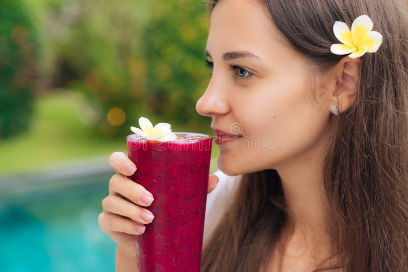 Het portret van mooi donkerbruin meisje met bloem in haar haar drinkt vers sap van draakfruit, zijaanzicht stock afbeeldingen