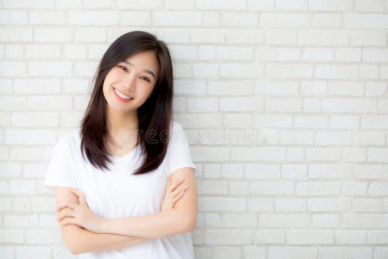 Het portret van mooi jong Aziatisch vrouwengeluk die zich op grijze cementtextuur grunge bevinden ommuurt baksteenachtergrond royalty-vrije stock afbeeldingen
