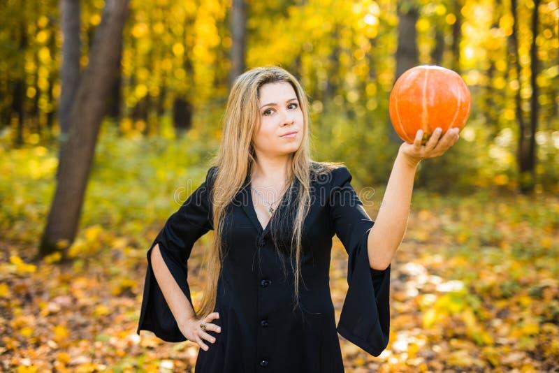 Het portret van mooi meisje als heks kleedde zich in een kleding met een kap Halloween, Carnaval, vakantie, de herfst en mensen stock afbeelding