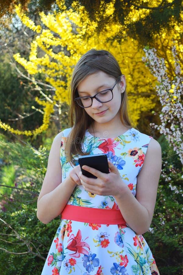 Het portret van mooi meisje met glazen en het bruine haar typen schrijven bericht op smartphone Jongelui die teneeger in de groen stock foto's