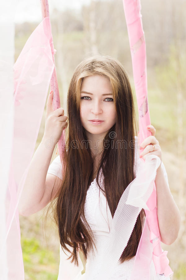 Het portret van mooie bruidvrouw in al wit doorboort in openlucht schommeling royalty-vrije stock foto