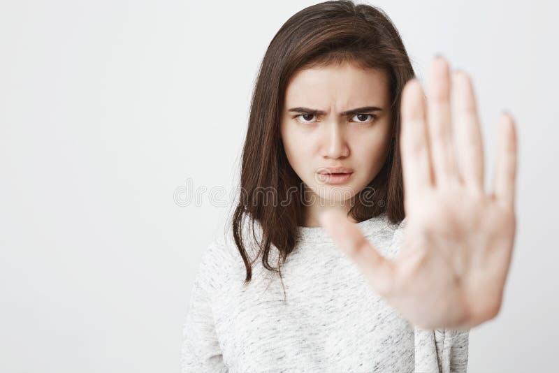 Het portret van mooie Europese vrouw met ernstige en boze uitdrukking die één uitrekken dient greep in of houdt gebaar tegen, ove royalty-vrije stock foto