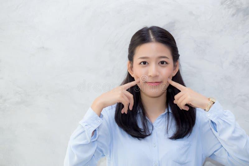 Het portret van mooie jonge Aziatische bevindende de aanrakingswang van het vrouwengeluk op grijze cementtextuur grunge ommuurt a stock fotografie