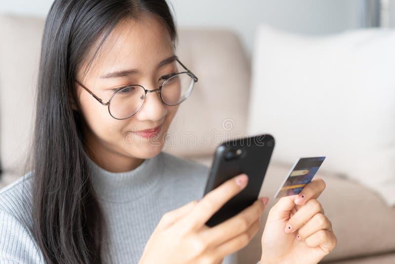 Het portret van Mooie jonge Aziatische vrouwen koopt online met een creditcard het meisje van Azië gebruikt smartphone en maakt o stock fotografie