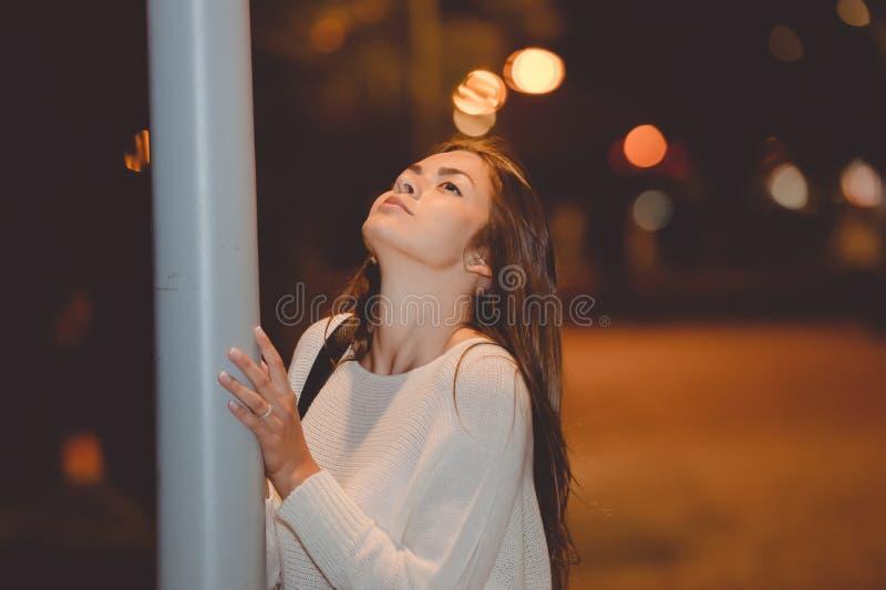 Het portret van mooie jonge dame, de post van de weglamp in de nacht, het gelijk maken steekt bokeh achtergrond aan royalty-vrije stock foto
