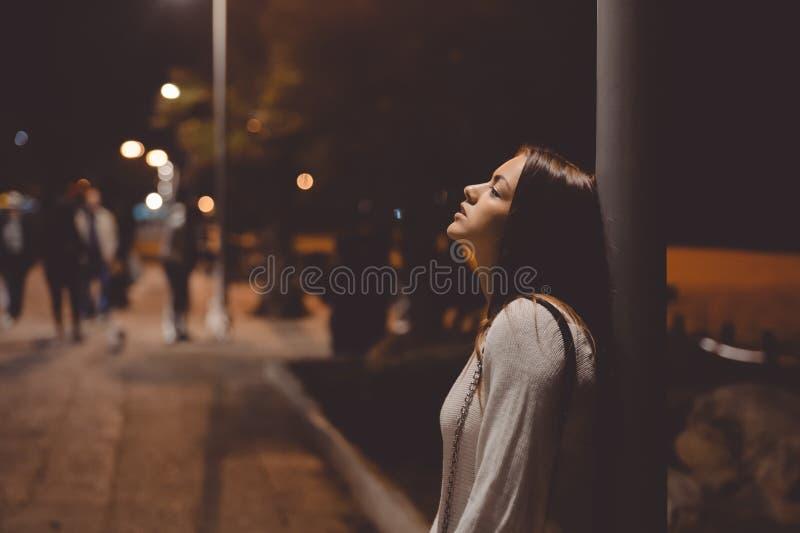 Het portret van mooie jonge dame die, stadsstraat in de nacht, het gelijk maken steekt in openlucht bokeh achtergrond aan omhoog  royalty-vrije stock afbeeldingen