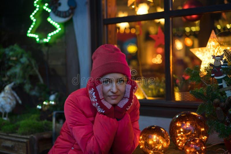 Het portret van mooie jonge glimlachende vrouw in rode hoed met defocused Kerstmislichten op de achtergrond royalty-vrije stock foto