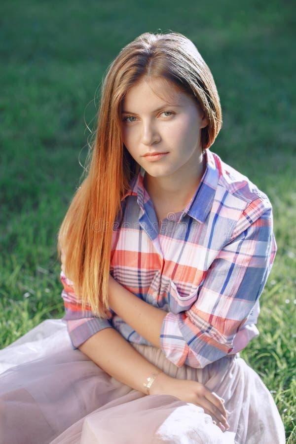 Het portret van mooie jonge Kaukasische vrouw met lang rood haar in plaidoverhemd en de roze tutu Tulle begrenzen, zittend op gra stock fotografie