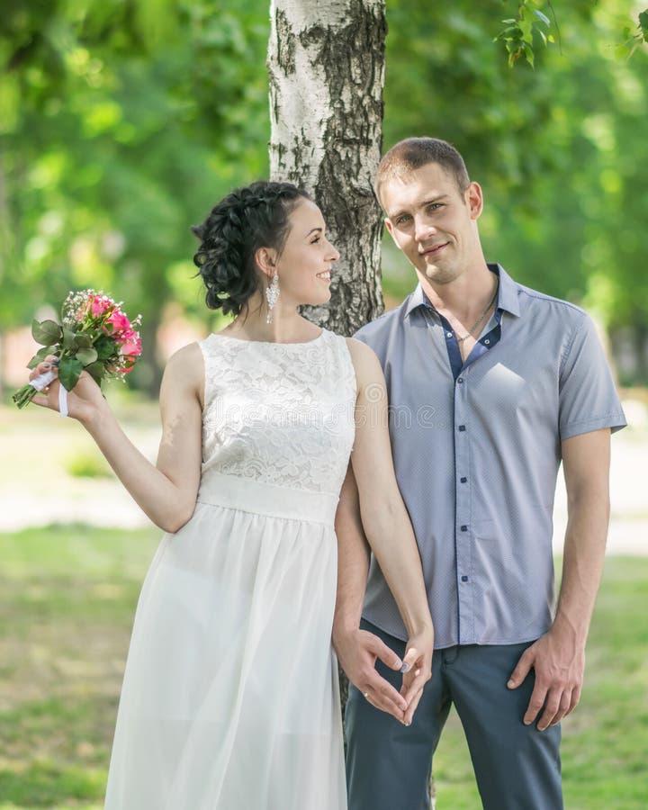 Het portret van mooie jonge paar vrouwelijke bruid met klein huwelijksroze bloeit rozenboeket en de mannelijke handen van de brui royalty-vrije stock foto