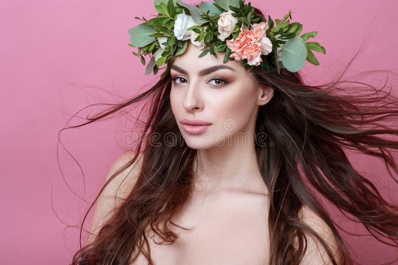 Het portret van mooie jonge seksuele sensuele vrouw met perfecte huid maakt omhoog stromende haar en bloemen op hoofd op roze ach royalty-vrije stock foto's