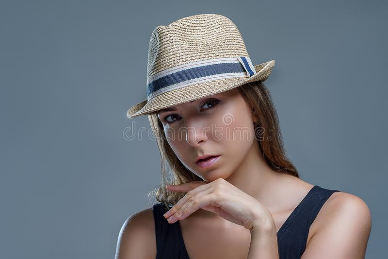 Het portret van mooie jonge vrouw in een modieuze hoed die isoleert dicht omhoog op grijze achtergrond in een studio, toevallige  stock afbeelding