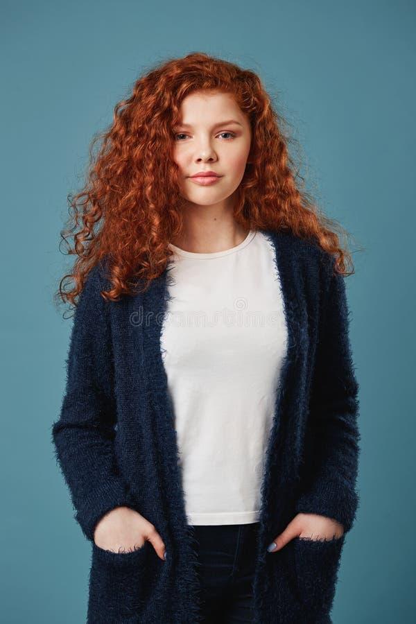 Het portret van het mooie meisje van de gemberstudent met golvend haar en sproeten het houden dient zakken in, kijkend in camera  stock afbeelding