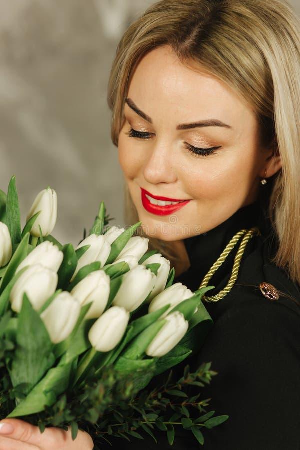 Het portret van mooie moeder houdt een boeket van witte tulpen op 8 van maart Bloemen in de hand van de vrouw Blond haarmamma royalty-vrije stock foto's