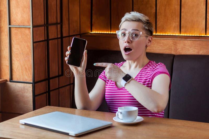 Het portret van mooie ongelooflijke jonge blogger met kort haar in roze t-shirt en oogglazen zit in koffie, houdend telefoon stock foto