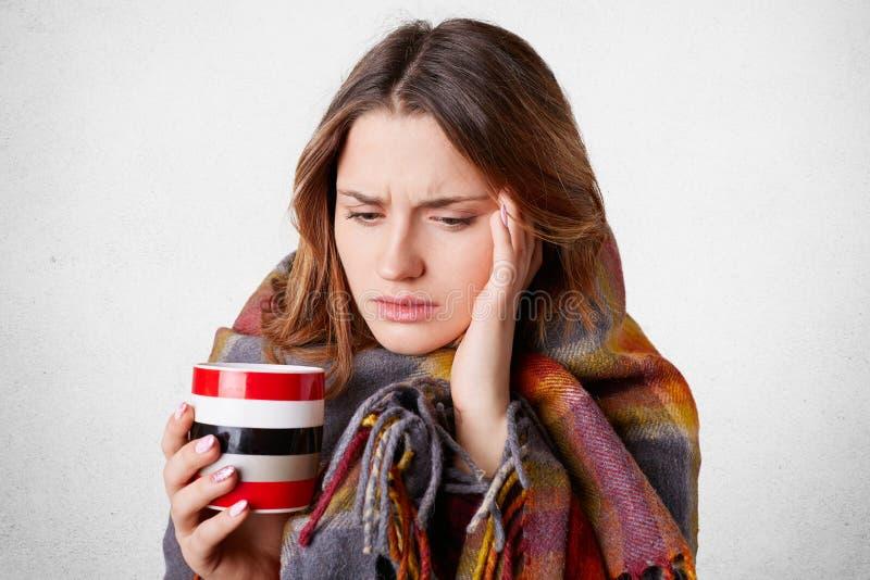 Het portret van mooie vrouw heeft hoofdpijn, heeft slechte koude, drinkt hete die thee of koffie, in geruite deken wordt de verpa stock fotografie