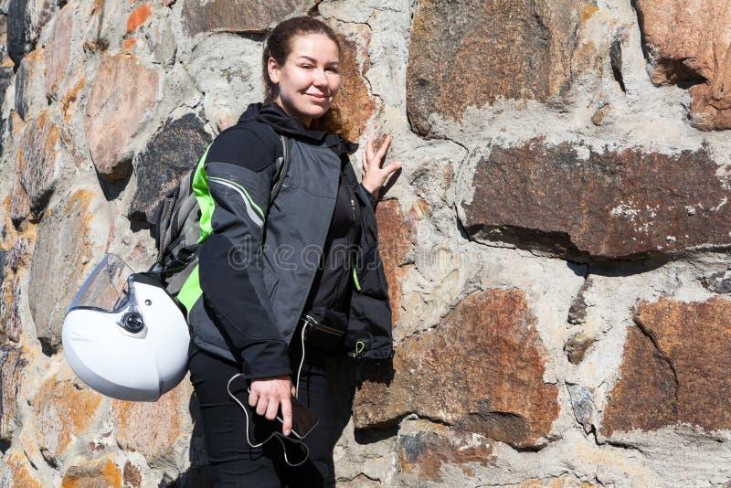 Het portret van motorrijdervrouw bevindt zich dichtbij steenmuur in kleding, met rugzak op haar rug en helm in bijlage aan het royalty-vrije stock foto