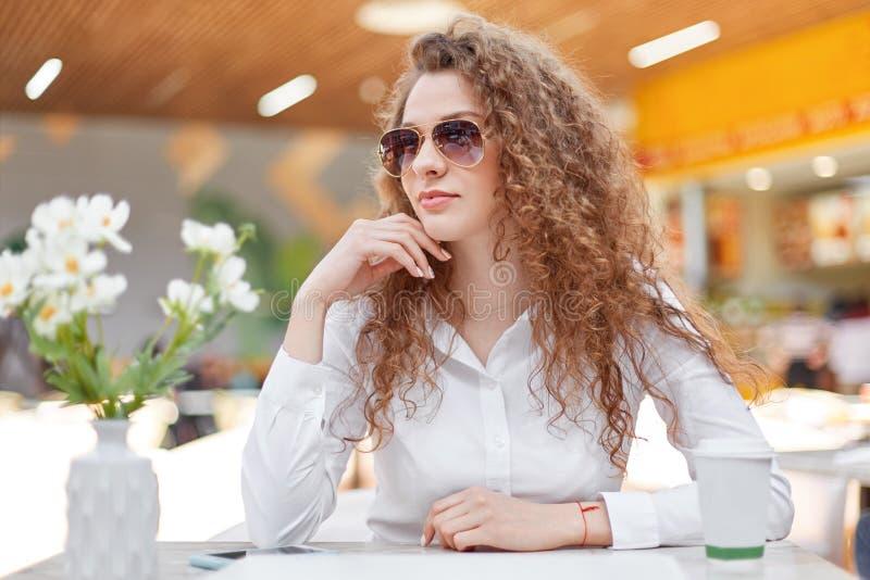 Het portret van nadenkende onderneemster draagt elegante blouse en de zonnebril, ziet weg eruit, zit in cafetaria zoals wacht op  royalty-vrije stock afbeelding