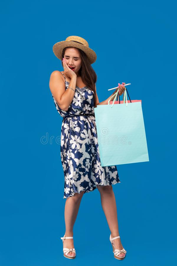 Het portret van het ongelukkige jonge vrouw kijken in haar portefeuille in winkelcentrum, besteedde teveel, niet genoeg contant g stock afbeelding
