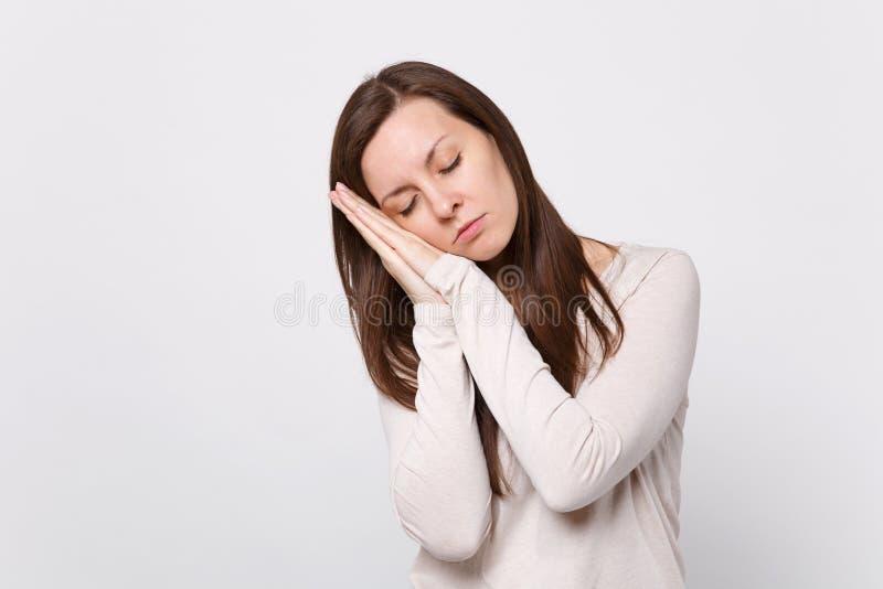 Het portret van ontspannen jonge vrouw in lichte kleren die ogen houden sloot, slapend met handen dichtbij gezicht op wit stock afbeeldingen