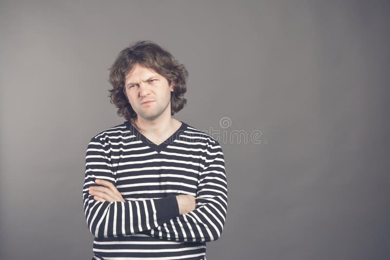 Het portret van ontstemd mannelijk model kijkt boos met sombere uitdrukking, houdt wapens gekruist, draagt gestreepte over geïsol stock fotografie