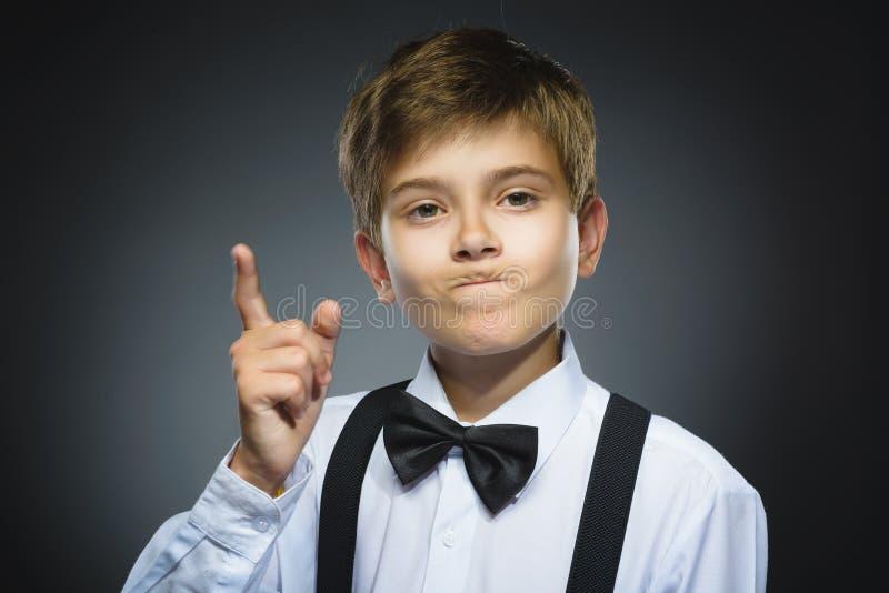 Het portret van ontstemde boze jongen met bedreigt vinger op grijze achtergrond close-up stock afbeelding