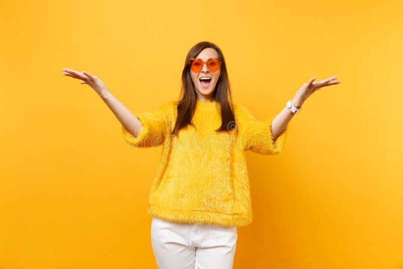 Het portret van opgewekte gelukkige vrouw die in bontsweater, witte broek en hart oranje glazen handen uitspreiden isoleerde op h stock fotografie