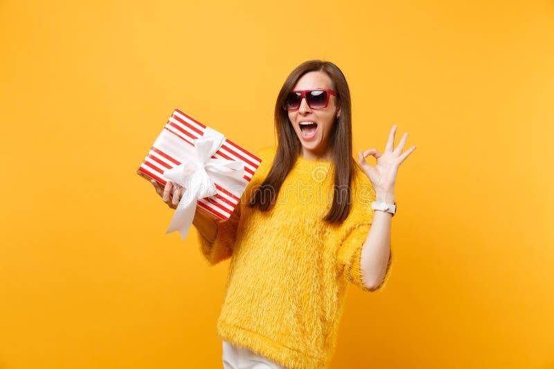 Het portret van Opgewekte jonge vrouw in rode oogglazen die O.K. teken tonen die rode doos met gift houden, stelt geïsoleerd op h stock foto