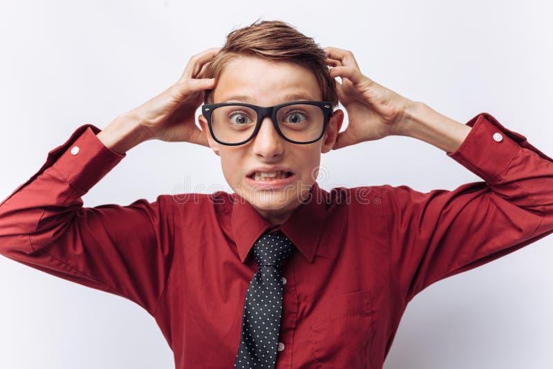 Het portret van positieve en emotionele schooljongen, toont irritatie, witte achtergrond, glazen, rood overhemd, bedrijfsthema, d royalty-vrije stock afbeelding
