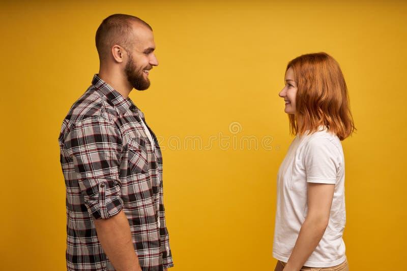 Het portret van het profiel zijaanzicht van aardig mooi charmant aantrekkelijk vrolijk flirty paar die elkaar bekijken bespreking stock foto's
