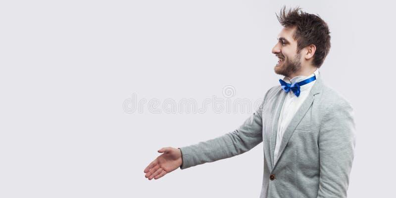 Het portret van het profiel zijaanzicht van de gelukkige knappe gebaarde mens in toevallig grijs en kostuum, blauwe vlinderdas di stock fotografie