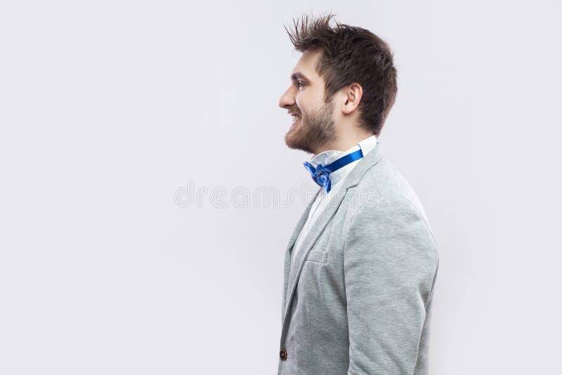 Het portret van het profiel zijaanzicht van de gelukkige tevreden knappe gebaarde mens in toevallig grijs en kostuum en blauwe vl royalty-vrije stock afbeelding