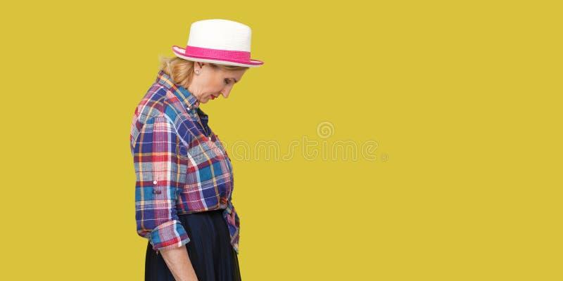 Het portret van het profiel zijaanzicht van droevige alleen modieuze rijpe vrouw in toevallige stijl met hoed status die, houdend stock fotografie