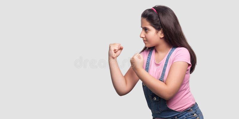 Het portret van het profiel zijaanzicht van ernstig of boos jong meisje in roze t-shirt en blauwe overall die zich met vuisten be stock fotografie