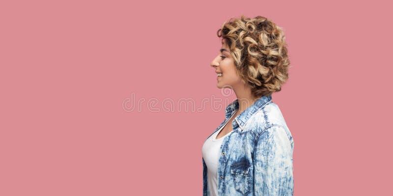 Het portret van het profiel zijaanzicht van jonge gelukkige vrouw met make-up en blonde krullend kapsel in toevallig blauw overhe stock afbeeldingen