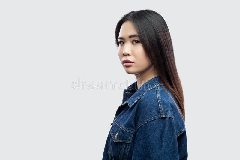 Het portret van het profiel zijaanzicht van kalme ernstige mooie donkerbruine Aziatische jonge vrouw in toevallig blauw denimjasj royalty-vrije stock fotografie