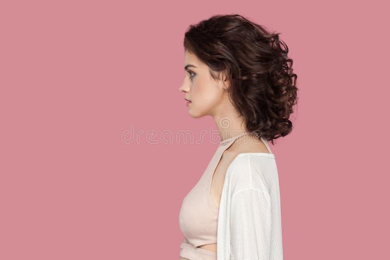 Het portret van het profiel zijaanzicht van kalme mooie donkerbruine jonge vrouw met krullend kapsel in toevallige stijl die zich stock foto's