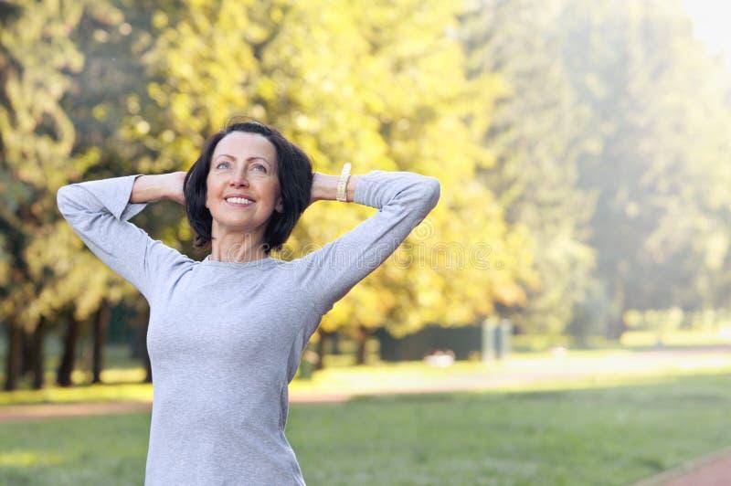 Het portret van rijpe vrouw vóór of na stoot in het park aan stock foto's