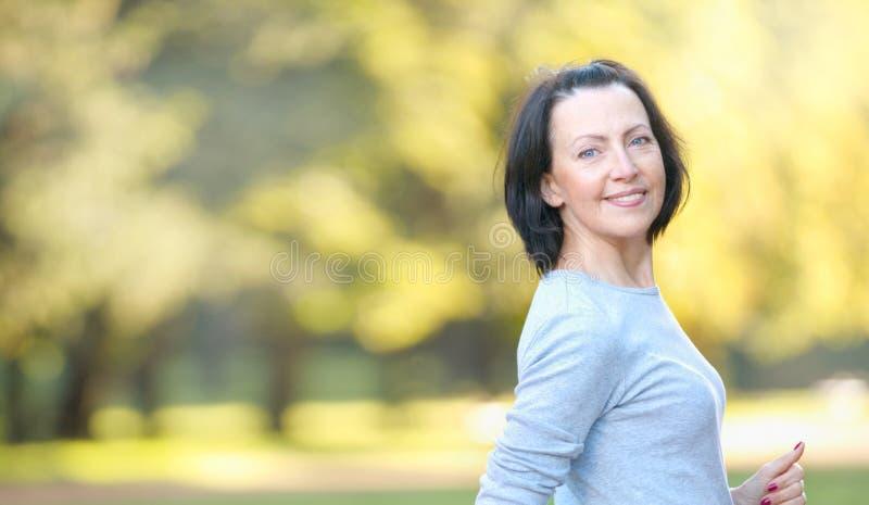 Het portret van rijpe vrouw weared in sportenkleren in het park royalty-vrije stock foto
