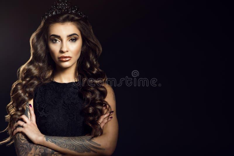 Het portret van schitterende glam tatoeeerde model met lang golvend zijdeachtig haar en provocatief maak omhoog het dragen van ka stock fotografie