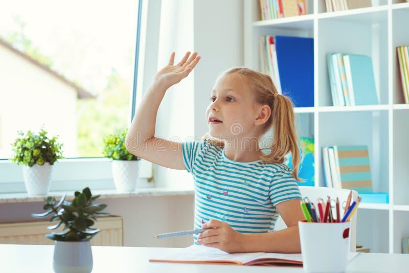 Het portret van schoolmeisje heft haar op indient classroon bij lesso stock foto