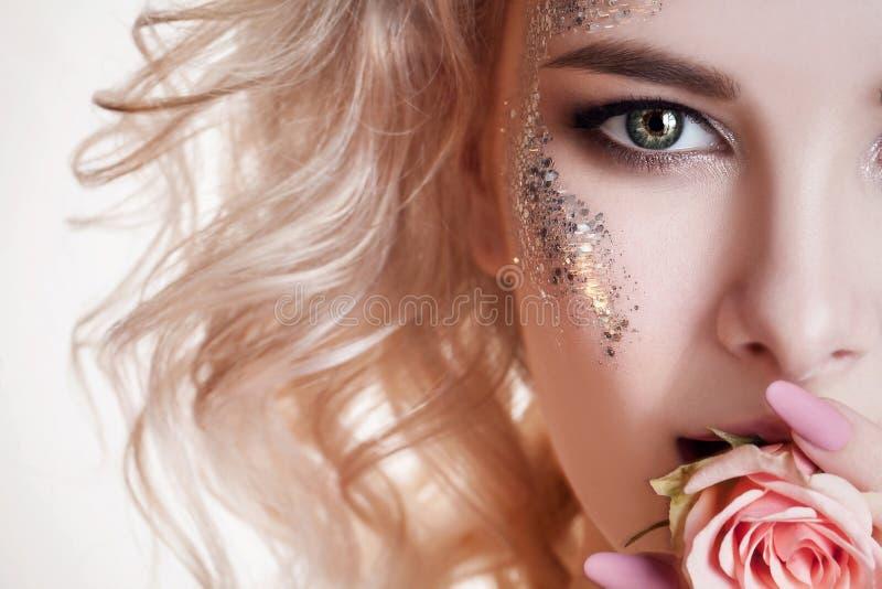 Het portret van schoonheidsvrouwen het halve gezicht van jonge krullende blonde vrouw met pastelkleurmanicure en de perfecte kuns royalty-vrije stock foto