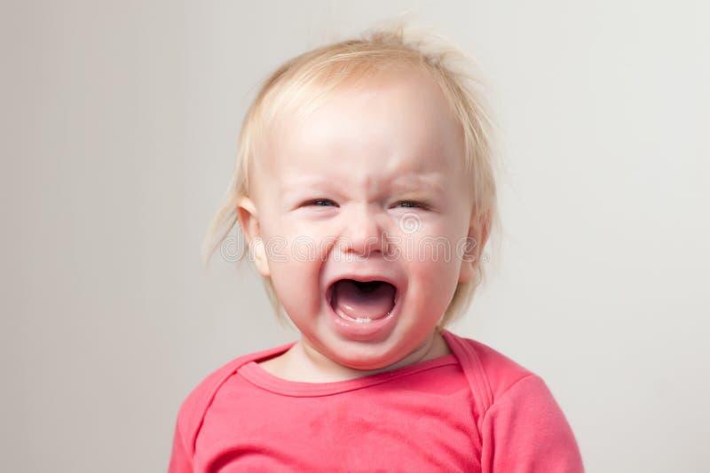 Het portret van schreeuwende jonge baby zit op stoel stock foto