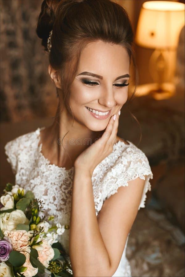 Het portret van sensueel en mooi donkerbruin modelmeisje met heldere make-up en het charmeren glimlachen en met boeket van bloeme royalty-vrije stock fotografie
