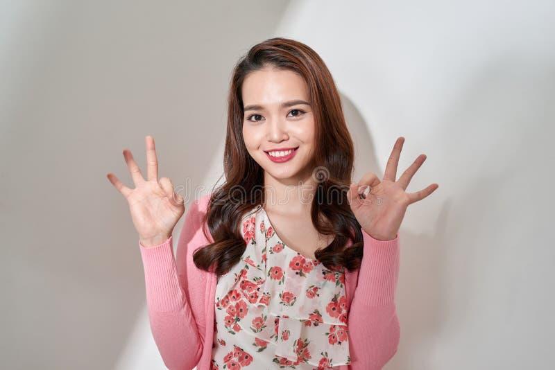 Het portret van sexy, charmant, mooi, aardig, in, lachend meisje in bloemen kleedt het tonen van twee o.k. teken met vingers, kni stock afbeeldingen