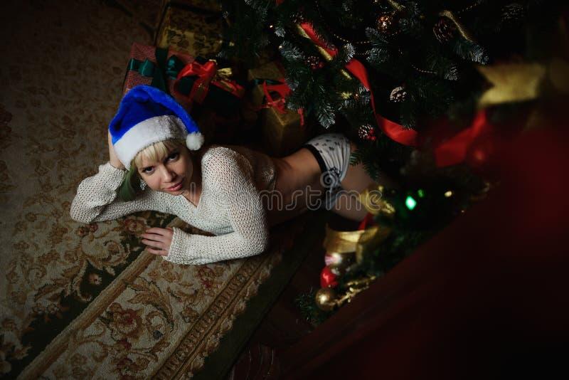 Het portret van sexy jong meisje ligt onder Kerstboom met voorstelt royalty-vrije stock afbeelding