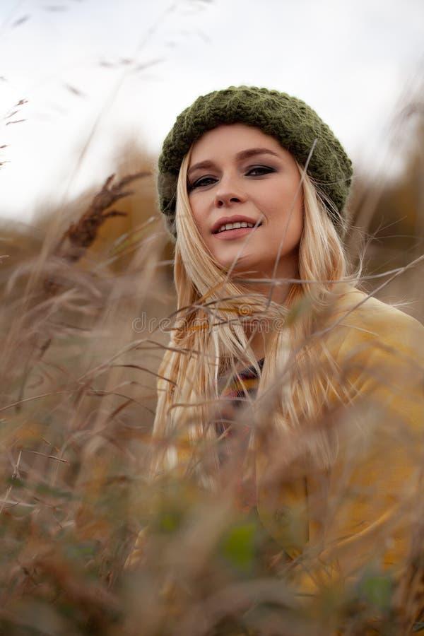 Het portret van sexy mooie vrouw in gebreide groene hoed en gele laag, smokeyogen maakt op, vliegend haren in droog gras stock afbeelding