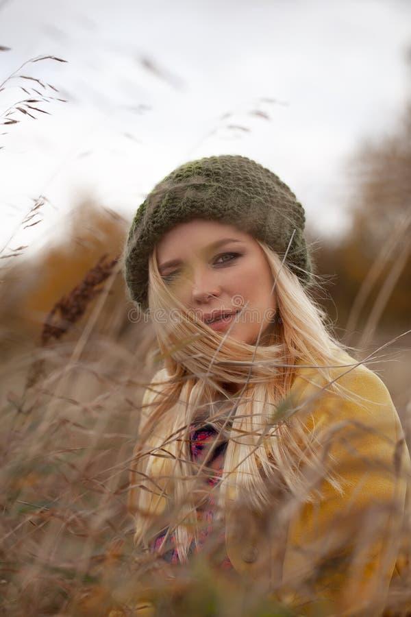 Het portret van sexy mooie vrouw in gebreide groene hoed en gele laag, smokeyogen maakt op, vliegend haren in droog gras stock fotografie