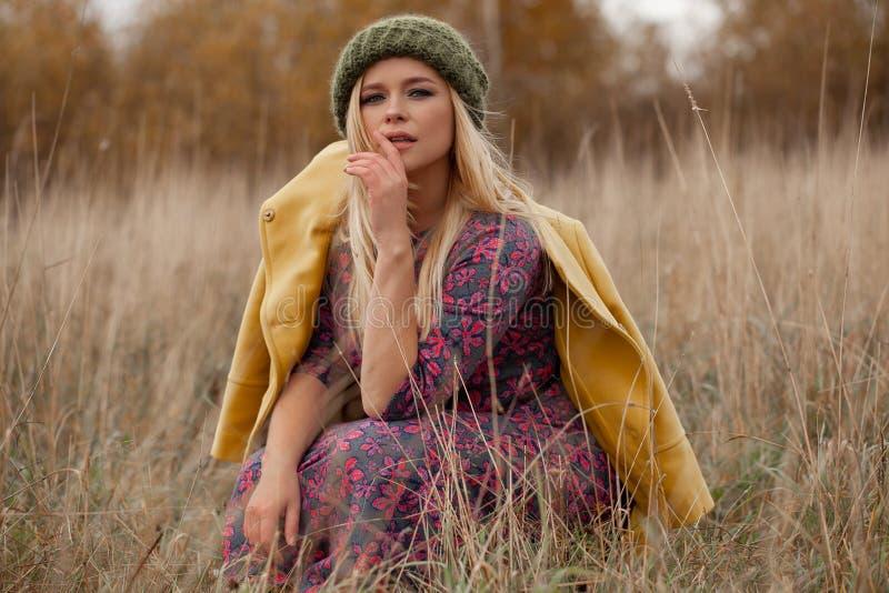 Het portret van sexy mooie vrouw in gebreide groene hoed en gele laag, smokeyogen maakt op, vliegend haren in droog gras stock afbeeldingen